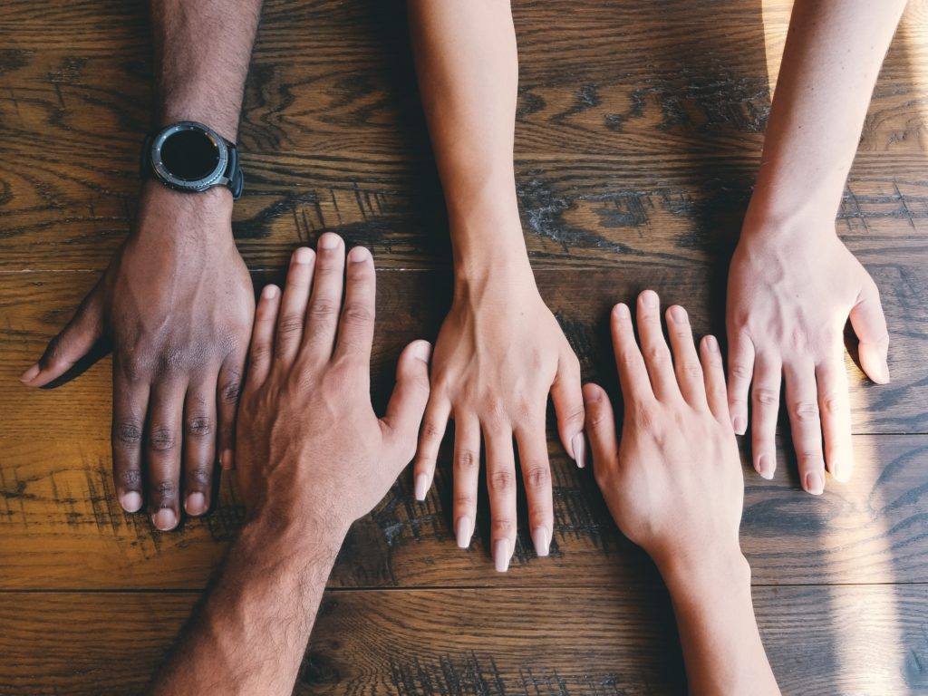 diverse hands together on table
